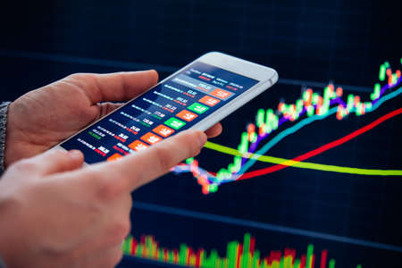 A trader or a financial analyst checking the recent stock exchange trends using the smartphone.