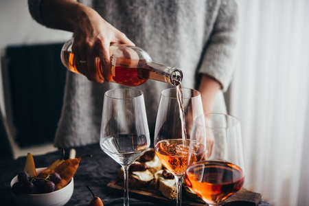 Pouring rose wine at a dinner party with friends.