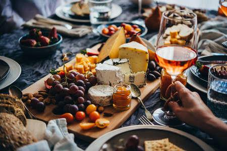 Freunde haben eine Dinnerparty mit verschiedenen Arten von Vorspeisen und Roséwein.