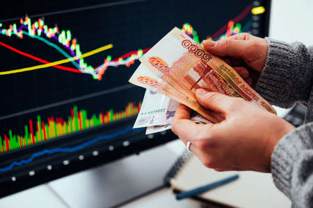 Hands holding russian currency roubles in front of the stock exchange screen showing trading graphics.