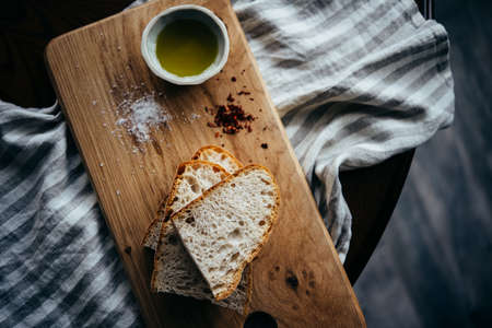 Classic Italian appetiser of bread and olive oil served on a wooden board.