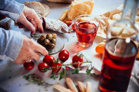 Preparing a traditional wine snack with cheese and different appetisers. Stock Photo
