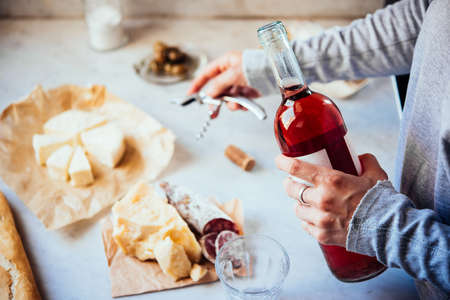 Hands opening the bottle of rose wine, cheese and snacks on the background.