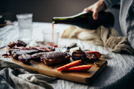 Pouring red wine for dinner with steaks and grilled vegetables. Healthy home eating concept
