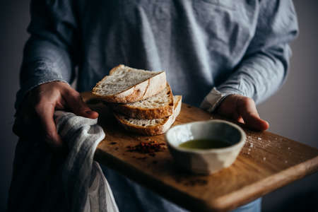 Hands holding a wooden board with artisanal bread and olive oil served for a snack. Stock Photo