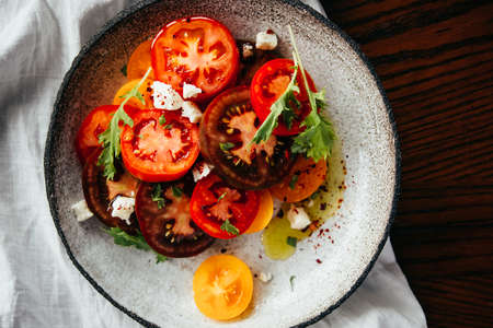 Tomato and cheese salad beautifully served on a ceramic plate. Healthy home dining concept.