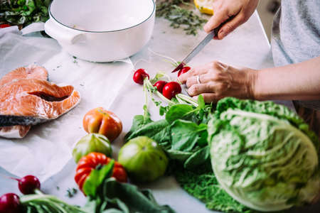 Making salad of cooking different vegetables and greens. Healthy eating concept.
