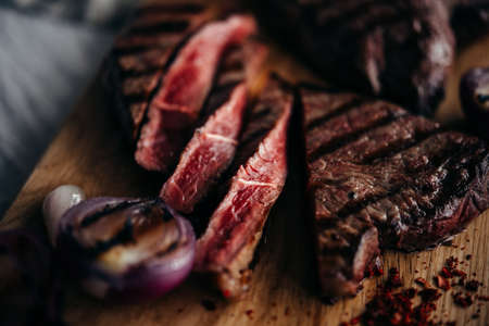 Close-up of medium rare beef steak served on a wooden board.