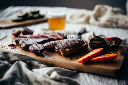 Pouring beer for dinner with steaks and grilled vegetables. Healthy home eating concept. Stock Photo