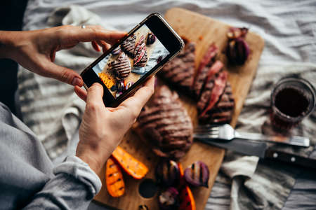 Taking a picture of some steaks and grilled vegetables with a mobile phone. Stock Photo