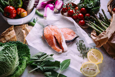 Salmon fish and different vegetables prepared for dinner cooking. Healthy eating concept. Stock Photo