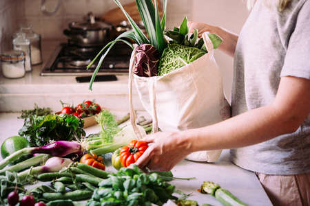 Unpacking a bag of fresh vegetables and greens after grocery shopping. Healthy eating concept.