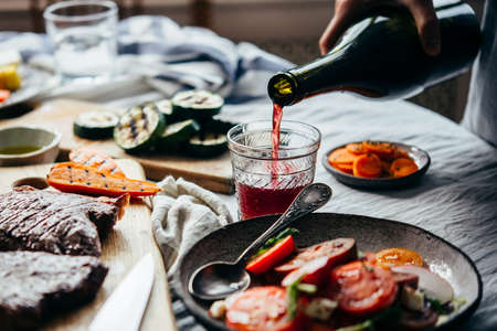 Pouring red wine for dinner with steaks and tomato salad. Healthy home eating concept.