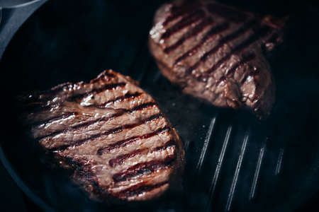 Making classic steaks on grill pan.