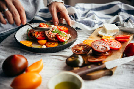 Making classic tomato salad. Healthy home dining concept.