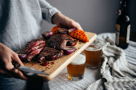 Serving a lunch with beef steaks, grilled vegetables and beer. Healthy home eating concept.