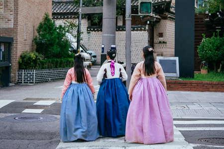 Ladies wearing traditional koran dresses walk along the streets of Seoul, South Korea.