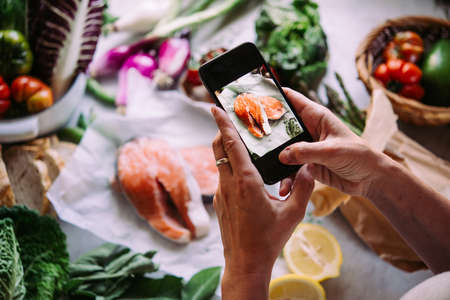 Taking picture of salmon fish and different beautiful vegetables and greens with a mobile phone. Stock Photo
