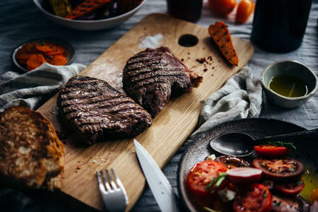 Steaks served on wooden board with tomato salad and grilled vegetables ready for dinner. Healthy home eating concept.
