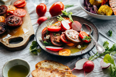 Different fresh tomatoes and greens on the table during cooking. Healthy eating concept. Stock Photo