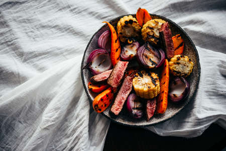 A steak and grilled vegetables salad with grilled vegetables ready for dinner. Healthy home eating concept.