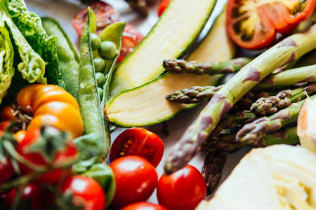 Different fresh vegetables and greens on the table before cooking. Healthy mediterranean eating concept.