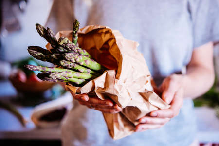 Hands holding a pack of asparagus. Healthy eating concept.