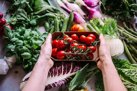 Hands holding a box of cherry tomatoes. Different fresh vegetables and greens on the table Stock Photo
