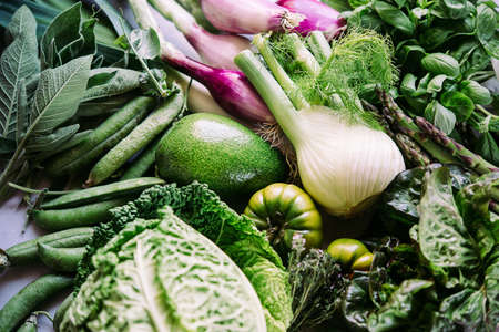 Different fresh vegetables and greens on the table before cooking. Healthy eating concept.