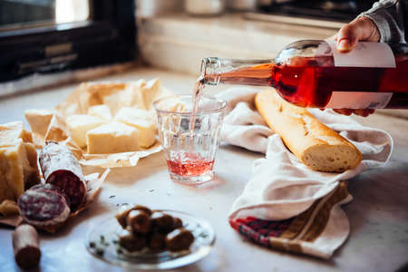 Pouring wine with cheese and snacks on the background.