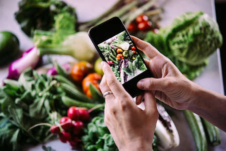 Taking picture of different beautiful vegetables and greens with a mobile phone. Stock Photo