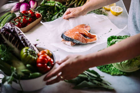 Cooking dinner with salmon fish and different vegetables. Healthy eating concept.
