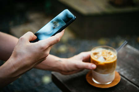 A person is taking a picture of iced latte in a coffeehouse with their smartphone