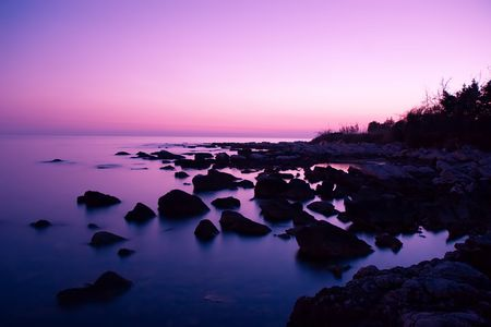 dimm: Fantastic scene of pink sky reflection at rocky bay