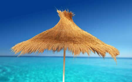 Relaxing on Tropical Beach under umbrella on sunny day Stock Photo