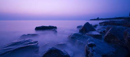 dimm: Fantastic scene of coast rocks in sea waves at sunset