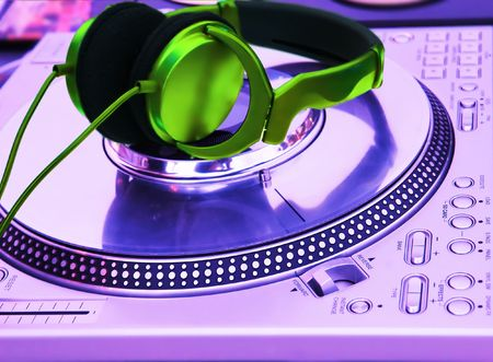 bpm: Professional DJ Vinyl Player with green Headphones on it
