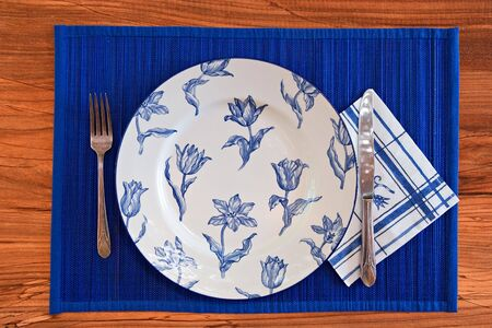 Elegant Blue Porcelain eating set with silverware on wooden background