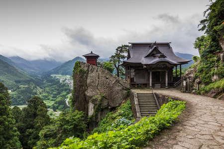 山寺仏教寺院の写真が背景の手前に、伝統的な木造建築を日本美しい田園風景