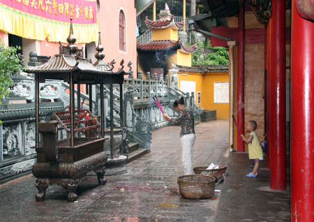 womna: A woman with a cild prays at the buddhist temple, Jiuhua Shan, China Editorial