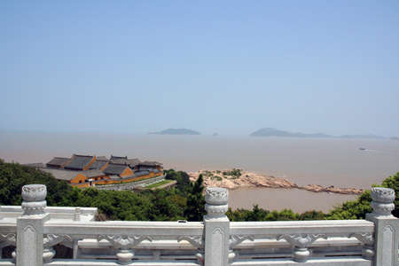 skie: A landscape with chinese buddhist temple overlooking the sea with some inslands in the disctance Stock Photo