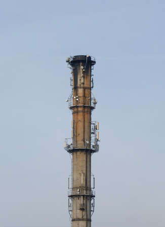 industrialization: A photo of an old unused, rusty and dirty, factory chimney, remnant of industrialization backgrounded against blue sky
