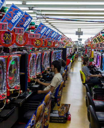The inside of a pachinko parlor in Osaka, Japan, with several players sitting at the machines  Redakční