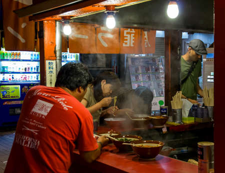 cuisine entertainment: Several people eating traditional japanese noodle soup - ramen - in a typical street bar in an entertainment district of Osaka, Dohtonbori
