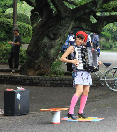 Street Musician - a japanese girl - plays the accordeon in Ueno park, Tokyo, Japan