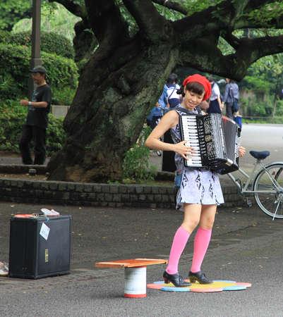 Street Musician - a japanese girl - plays the accordeon in Ueno park, Tokyo, Japan  新聞圖片