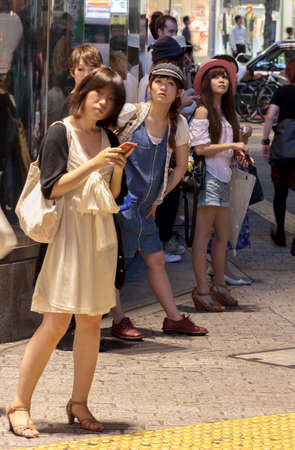 centres: Kyoto, Japan - June 28, 2010  Young, fashionable Japanese women stand near Shibuya Crossing on 28 June, 2010 in Tokyo, Japan  Shibuya is a traditional shopping district in Tokyo