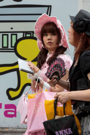 subcultures: Tokyo, Japan - June 2010  Gothic lolita in a pink dress with a hood walks in  Harajuku district in June 2010 in Tokyo  Harajuku district is a traditional meeting place for young people in Tokyo