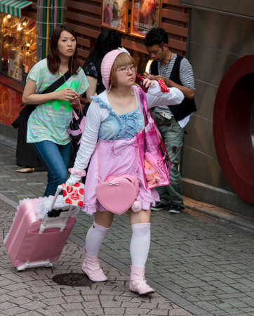 subcultures: Tokyo, Japan - June 2010  A young Japanese girl dressed in pink in a kawaii style walks in the street in Harajuku district in June 2010 in Tokyo  Harajuku district is a traditional meeting place for young people in Tokyo  Editorial