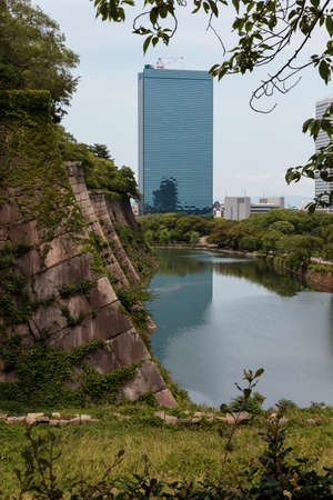 osaka castle: The moat of Osaka Castle with modern buildings in the distance, Japan
